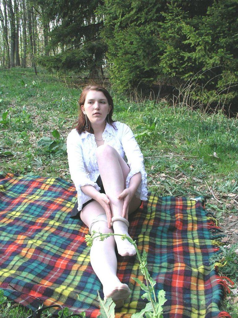Junge Frau sitzt auf Picknickdecke