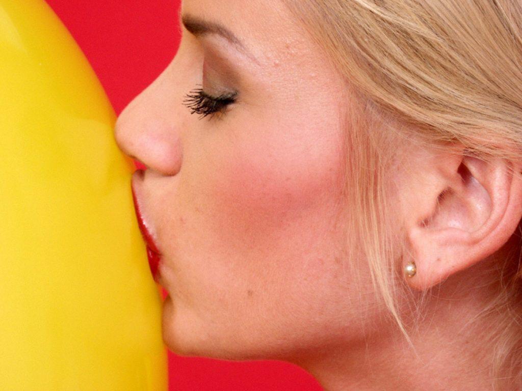 Frau küsst Luftballon
